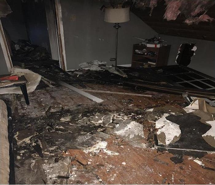 Burned bedroom with blackened walls and ruined floors