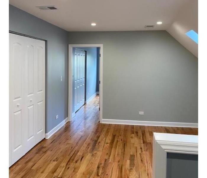 New bedroom with hardwood floors and freshly painted blue walls.