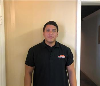 Male crew member in front of tan wall in SERVPRO shirt